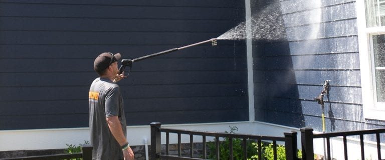 Pressure washing a residential building